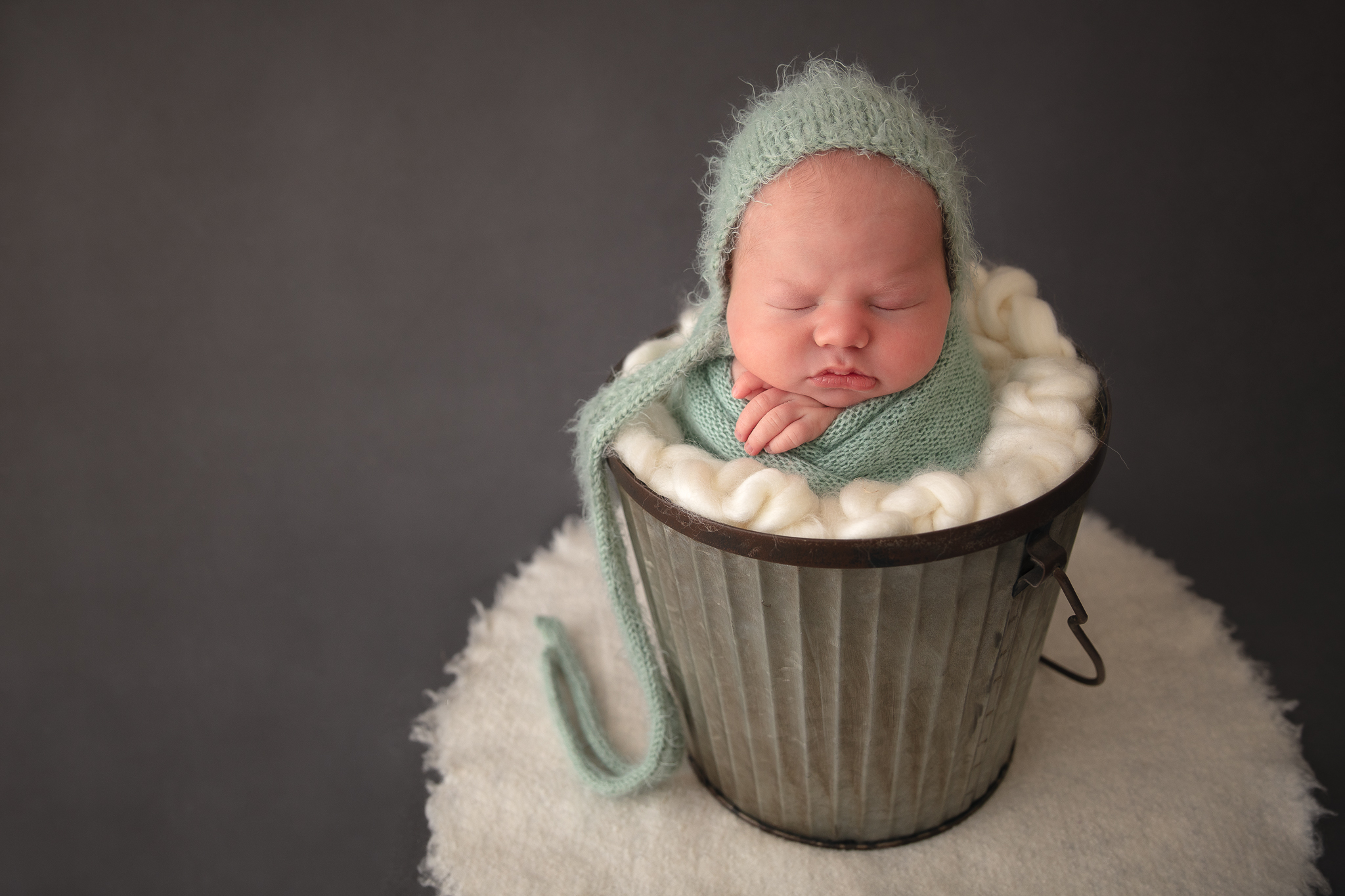 cute-boy-wrapped-newborn-photography-green-setup